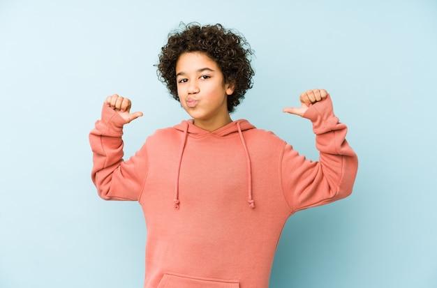 Menino afro-americano isolado se sente orgulhoso e autoconfiante, exemplo a seguir.