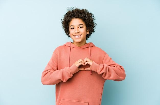 Menino afro-americano isolado sorrindo e mostrando uma forma de coração com as mãos.