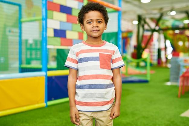 Menino afro-americano posando no play center
