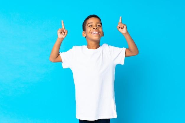 Menino afro-americano sobre azul isolado apontando uma ótima idéia