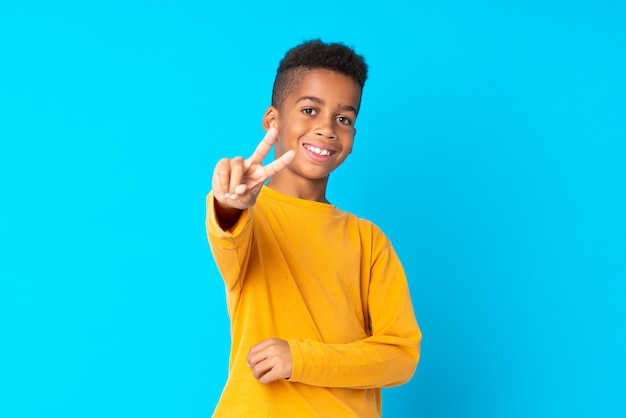 Menino afro-americano sobre isolado sorrindo e mostrando sinal de vitória
