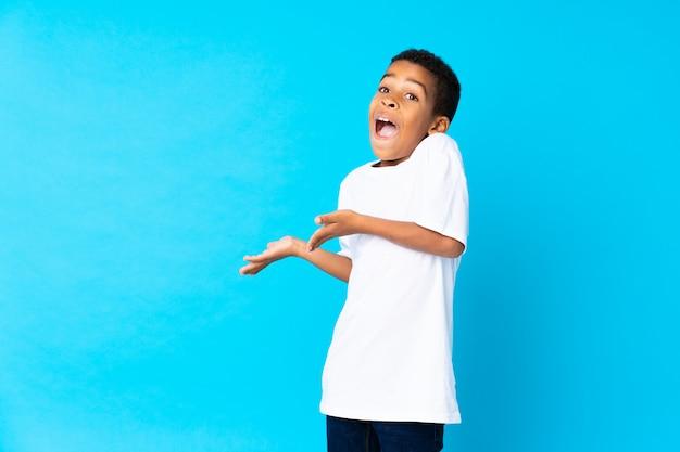 Menino afro-americano sobre parede azul isolada com expressão facial de surpresa