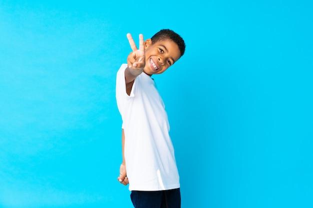 Menino afro-americano sobre parede azul isolada, sorrindo e mostrando sinal de vitória