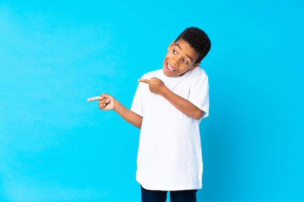 Menino afro-americano sobre parede azul isolada surpreendeu e apontando o lado