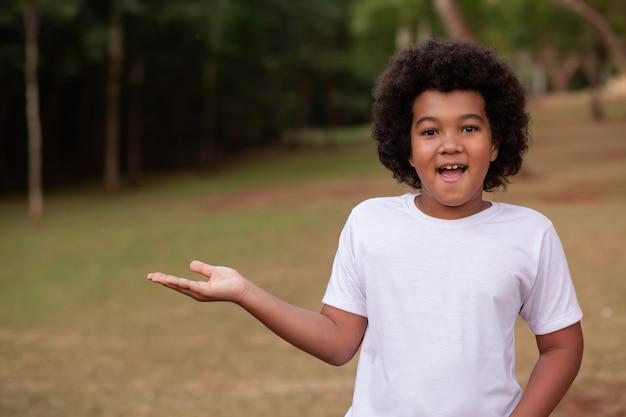 Menino afro com no parque com espaço para texto.