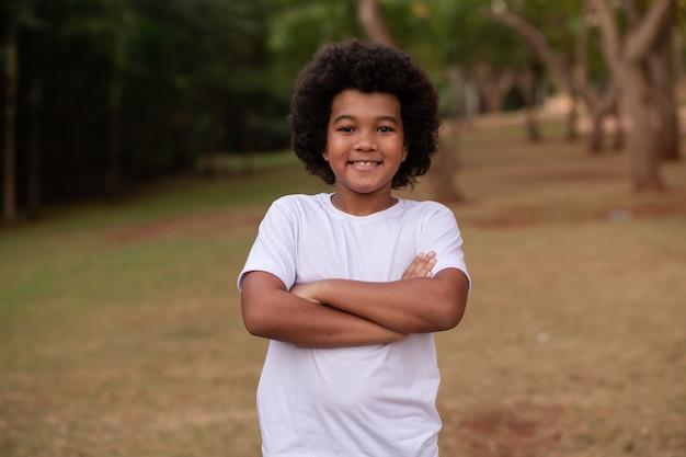 Menino afro com os braços cruzados com o parque ao fundo.