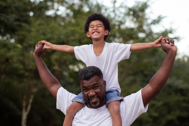 Menino afro com seu pai no parque em seu pescoço
