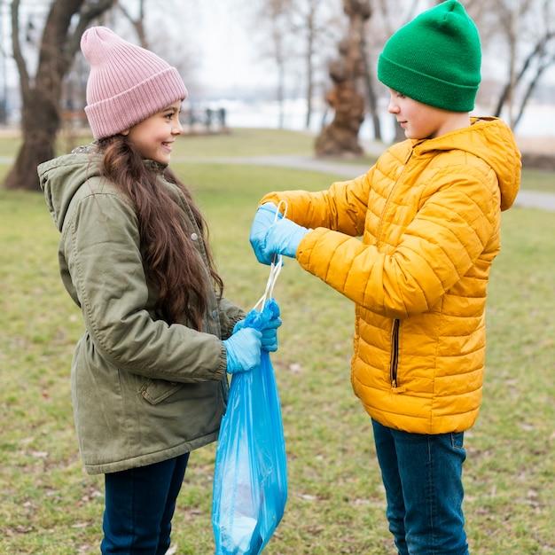 Menino ajuda menina fazendo um nó no saco de plástico