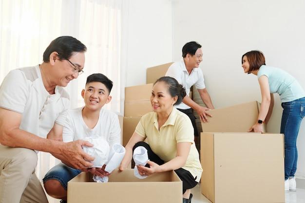 Menino ajudando avós a empacotar pertencentes