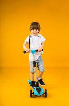 Menino alegre anda de scooter em uma superfície amarela com um lugar para texto. esportes para crianças