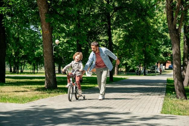 Menino alegre andando de bicicleta com o pai correndo perto da estrada cercada por gramados verdes e árvores em um parque público no verão