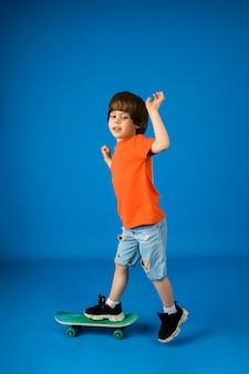 Menino alegre andando de skate em uma superfície azul com um lugar para texto
