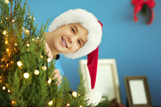 Menino alegre com árvore de natal em quarto decorado, close-up