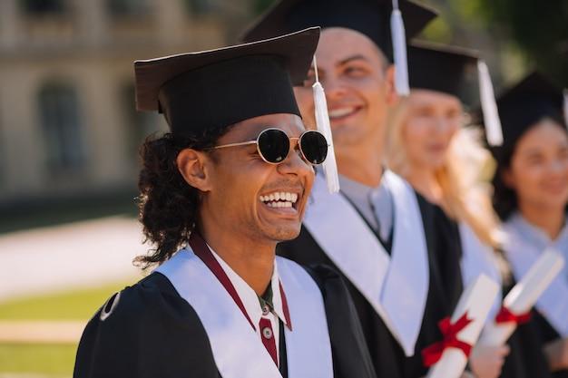 Menino alegre com boné de mestre e óculos escuros em frente aos amigos da universidade