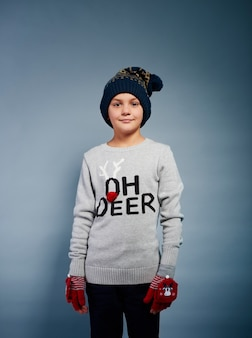 Menino alegre com luva e chapéu de tricô