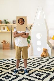 Menino alegre com uma caixa de papelão na cabeça através de um buraco redondo enquanto está de pé no tapete da sala de estar