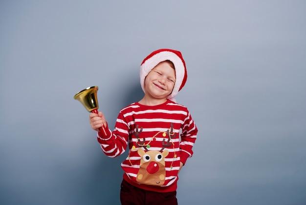 Menino alegre com uma campainha em estúdio.