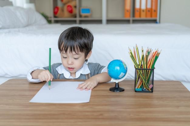 Menino alegre com uso de lápis de cor, desenho em papel branco