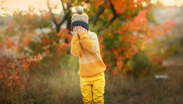 Menino alegre criança em roupas quentes fica na frente da câmera e caretas