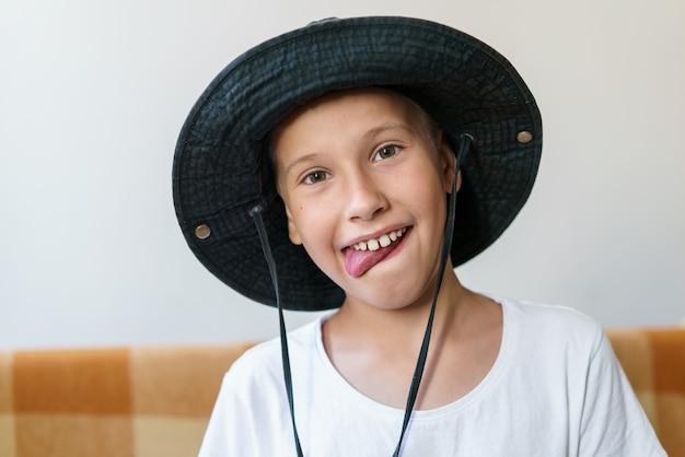 Menino alegre da escola em camiseta branca e chapéu preto senta no sofá e faz uma careta divertida ...