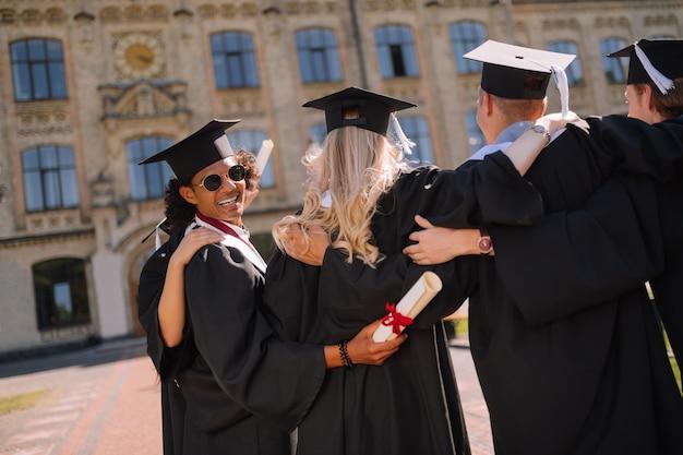 Menino alegre de óculos escuros abraçando seus colegas de grupo após a formatura no pátio da universidade
