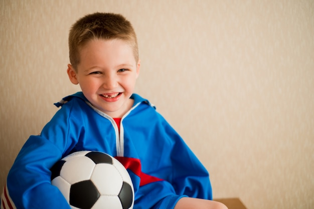 Menino alegre de riso com um futebol em um uniforme azul do esporte.