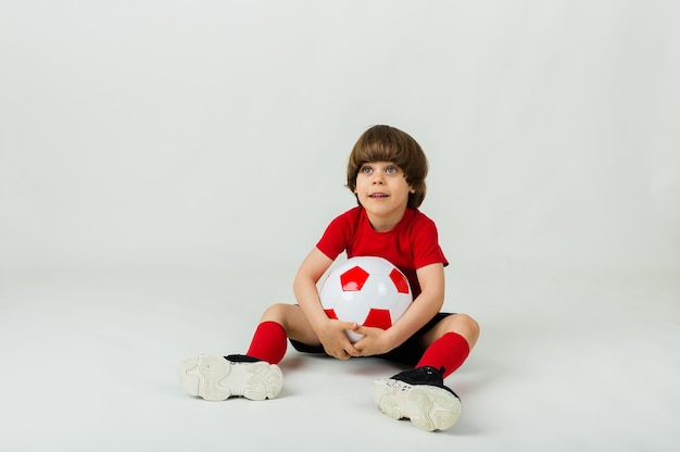 Menino alegre de uniforme sentado com uma bola de futebol em uma superfície branca com espaço para texto