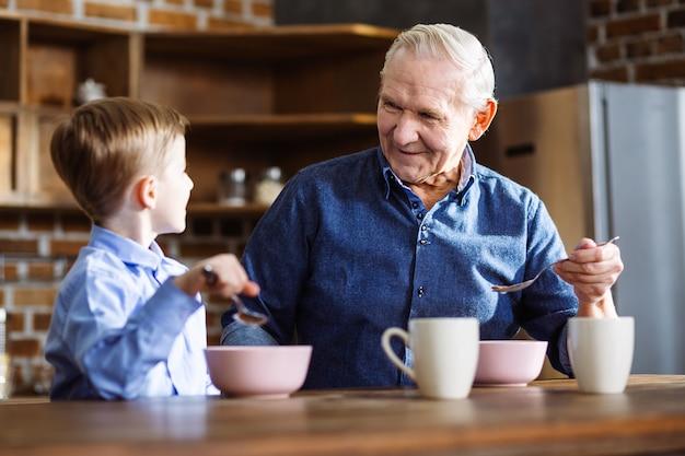 Menino alegre e avô tomando um café da manhã saudável enquanto estão sentados na cozinha