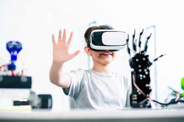Menino alegre e engenhoso usando um dispositivo de realidade virtual enquanto faz experiências com sua criação robótica em casa