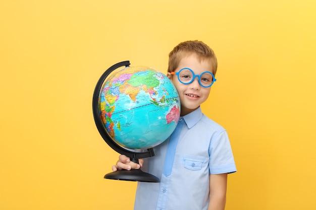 Menino alegre e feliz, uma criança, um estudante de óculos com um globo nas mãos