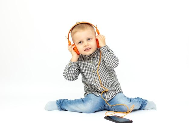 Menino alegre e sorridente ouvindo música em fones de ouvido