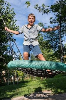 Menino alegre e travesso balançando em um balanço do playground público. criança brincar ao ar livre num dia quente de verão ensolarado.