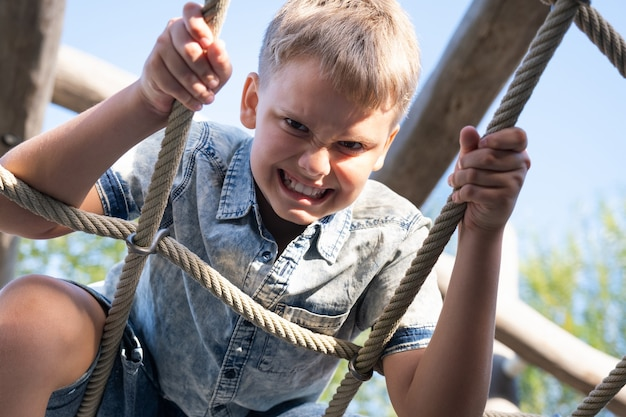 Menino alegre e travesso fazendo caretas e olhando para a câmera enquanto brinca no parquinho