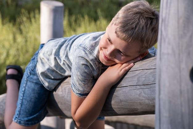 Menino alegre e travesso se divertindo em um parque infantil de madeira ao ar livre.