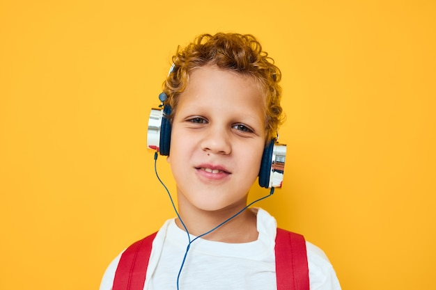 Menino alegre em fones de ouvido música mochila fundo amarelo