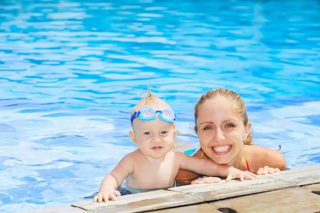 Menino alegre em óculos subaquáticos com mãe feliz na piscina