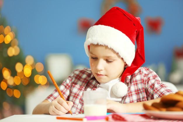 Menino alegre escrevendo uma carta para o papai noel, close-up