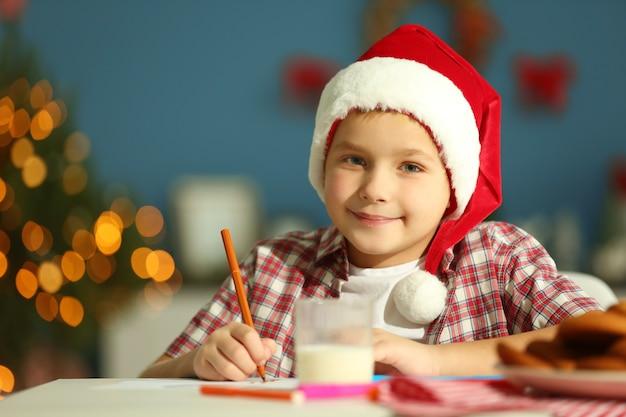 Menino alegre escrevendo uma carta para o papai noel