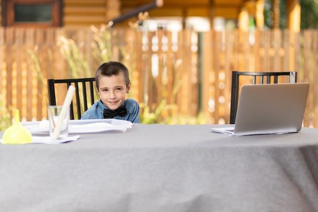 Menino alegre estudante está envolvido em aulas através de um laptop em casa no jardim. aulas online para crianças