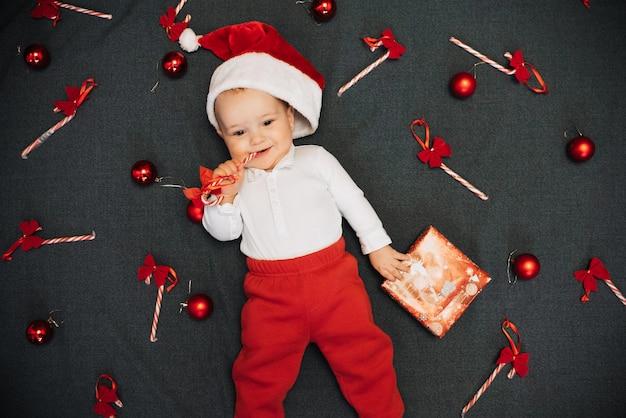 Menino alegre feliz no chapéu de papai noel, sorrindo entre bastões de doces de natal