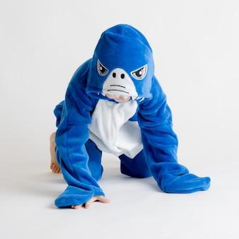 Menino alegre posando em um fundo branco em traje de pijama, tubarão azul
