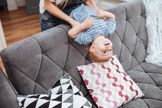 Menino alegre se divertindo com a mãe no sofá em casa
