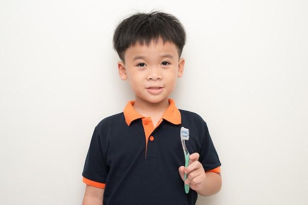 Menino alegre segurando uma escova de dentes sobre fundo branco, retrato de estúdio de um menino saudável de raça mista com uma escova de dentes isolada.