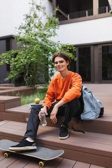 Menino alegre sentado com um skate e passando um tempo feliz no pátio da universidade