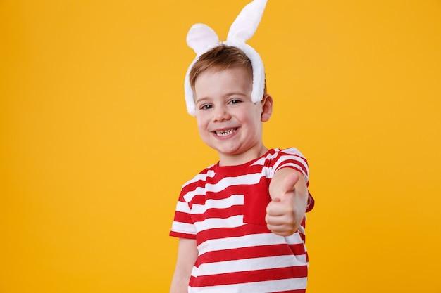 Menino alegre usando orelhas de coelho e mostrando os polegares