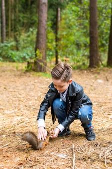 Menino alimenta o esquilo com nozes no verão na floresta