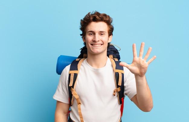 Menino alpinista sorrindo e parecendo amigável, mostrando o número cinco ou quinto com a mão para a frente, em contagem regressiva