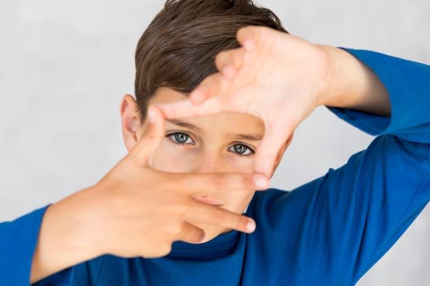 Menino alto ângulo, fazendo um quadro, com, seu, dedos