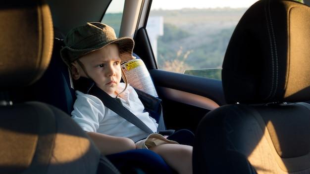 Menino amarrado em um assento à prova de crianças na parte traseira do carro para sua segurança e proteção