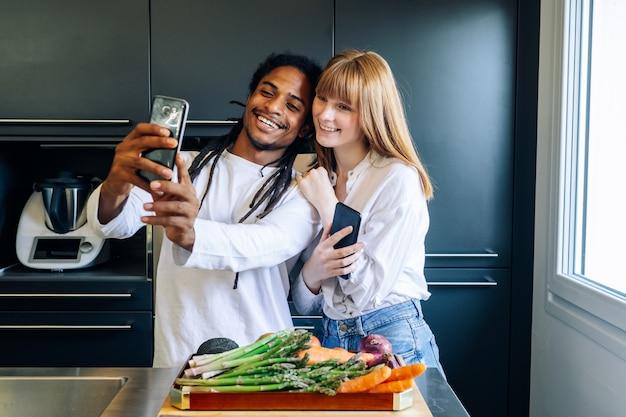 Menino americano africano, e, menina branca, fazendo, um, selfie, cozinha
